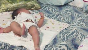 Le bébé asiatique se trouve sur un lit et apprendre à rouler de nouveau à l'estomac banque de vidéos