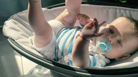 Le bébé avec du charme avec le simulacre détend dans le berceau banque de vidéos