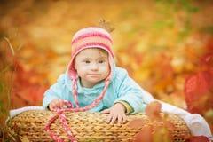 Le bébé avec la trisomie 21 se repose dans la forêt d'automne photos stock