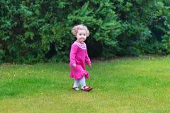 Le bébé avec le rose de port de cheveux bouclés a tricoté la robe Images libres de droits