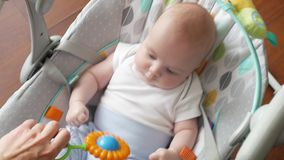 Le bébé balance dans une oscillation électronique avec un enfant jouant avec un hochet le bébé commence à pleurer banque de vidéos