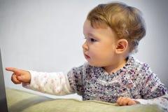 Le bébé curieux dirige son doigt photo stock