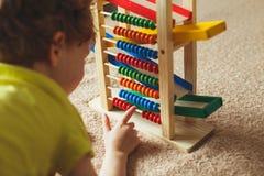 Le bébé d'élève du cours préparatoire apprend à compter Enfant mignon jouant avec le jouet d'abaque Petit garçon ayant l'amusemen Image stock