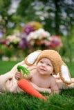 Le bébé dans le chapeau aiment un lapin avec le jouet de carotte sur l'herbe verte Photographie stock libre de droits