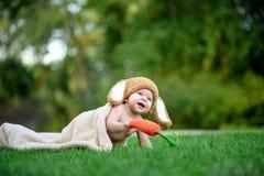 Le bébé dans le chapeau aiment un lapin avec le jouet de carotte sur l'herbe verte Images libres de droits