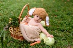 Le bébé dans le chapeau aiment un lapin avec le jouet de carotte sur l'herbe verte Photographie stock