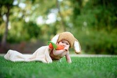Le bébé dans le chapeau aiment un lapin avec le jouet de carotte sur l'herbe verte Images stock