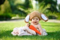Le bébé dans le chapeau aiment un lapin avec le jouet de carotte sur l'herbe verte dehors Photographie stock