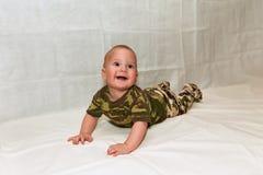 Le bébé dans le camouflage vêtx sur un fond blanc Image stock