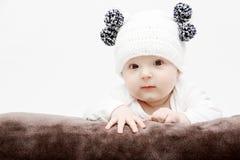 Le bébé dans le chapeau blanc se trouve sur le lit Photo stock