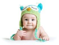 Le bébé dans le hibou drôle a tricoté le hibou de chapeau sur le fond blanc Photographie stock libre de droits