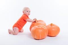 Le bébé dans le T-shirt orange sur un fond blanc s'assied à côté du pumpki image stock