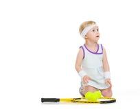 Le bébé dans le tennis vêtx avec la raquette et les boules Photo stock