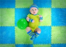 Le bébé dans les sports costument le mensonge sur un tapis de jeu image libre de droits