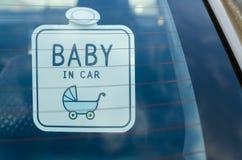 Le bébé dans le panneau de voiture se connectent le verre de voiture de retour photographie stock libre de droits
