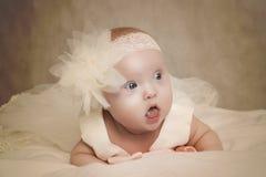 Le bébé dans une robe se trouve sur un oreiller Photo stock