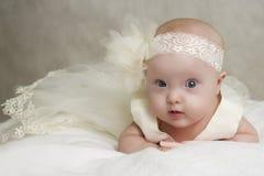 Le bébé dans une robe se trouve sur un oreiller Image stock