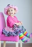 le bébé de 11 mois dans rose rectifient-vers le haut des vêtements Images libres de droits