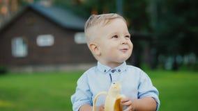Le bébé de 1 an gai mange une banane Il ` s se tenant au dos de la maison Images libres de droits