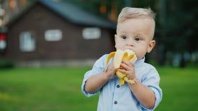 Le bébé de 1 an gai mange une banane Il ` s se tenant au dos de la maison Image stock