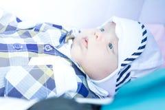 Le bébé de six mois se situe dans une poussette et regarde autour Photographie stock libre de droits