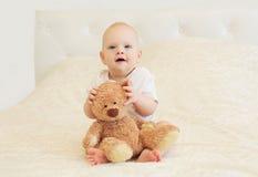 Le bébé de sourire heureux jouant avec le nounours concernent la maison de lit Image stock