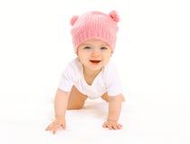 Le bébé de sourire mignon heureux dans le chapeau rose tricoté rampe sur le blanc Image libre de droits