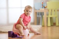 Le bébé de sourire s'asseyant sur le pot de chambre avec du papier hygiénique roulent Photographie stock