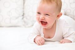 Le bébé de sourire se situent dans le lit Photos stock