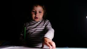 Le bébé dessine avec un crayon et montre un dessin, plan rapproché banque de vidéos