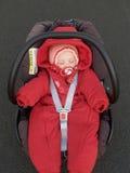 Le bébé dort dans un siège de voiture du ` s d'enfants Photo stock