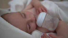 Le bébé dort gentiment avec une bouteille près de sa bouche, mouvement lent banque de vidéos