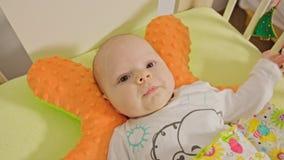 Le bébé doux se trouve sur un dos Photo stock