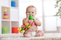 Le bébé drôle dans la couche-culotte s'assied sur le tapis et joue avec le jouet à la maison Profondeur de zone Photographie stock libre de droits