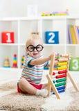 Le bébé drôle de crèche weared des lunettes avec l'abaque image stock