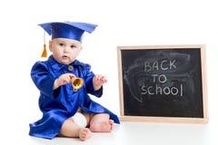 Le bébé drôle avec la cloche dans l'académicien vêtx à Images libres de droits