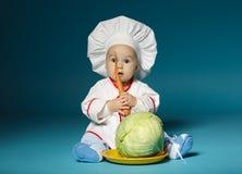 Le bébé drôle avec le costume de cuisinier tient la carotte Photos libres de droits
