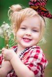 Le bébé en ressort fleurissant fait du jardinage des pissenlits Photographie stock