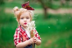 Le bébé en ressort fleurissant fait du jardinage des pissenlits Photographie stock libre de droits