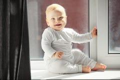 Le bébé espiègle s'assied sur le rebord de fenêtre dans des combinaisons blanches Photos libres de droits
