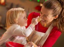 Le bébé essayant d'enduire des mères flairent avec de la farine Photo libre de droits