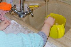Le bébé essuie de petites tasses après lavage Image libre de droits