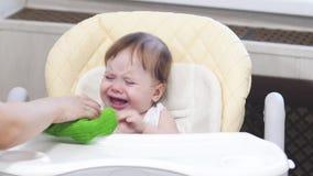 Le bébé est se reposer capricieux et pleurant sur le highchair dans la cuisine banque de vidéos