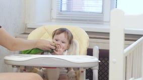 Le bébé est se reposer capricieux et pleurant sur le highchair dans la cuisine clips vidéos