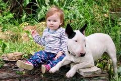 Le bébé et le chien femelles mignons heureux s'assied dans le jardin L'enfant joue avec le chien blanc de bull-terrier anglais de Photos stock