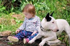 Le bébé et le chien femelles mignons heureux s'assied dans le jardin L'enfant joue avec le chien blanc de bull-terrier anglais de Photo stock