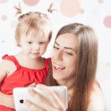 Le bébé et la mère drôles font le selfie au téléphone portable Photographie stock libre de droits