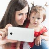 Le bébé et la mère drôles font le selfie au téléphone portable Photos stock