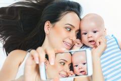 Le bébé et la mère drôles font le selfie au téléphone portable Images stock
