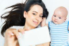 Le bébé et la mère drôles font le selfie au téléphone portable Image libre de droits